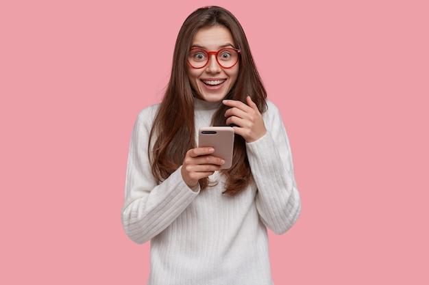 Hermosa mujer sonriente envía un mensaje en el teléfono celular moderno, estando de buen humor, vestida de manera informal, conectada a internet inalámbrico