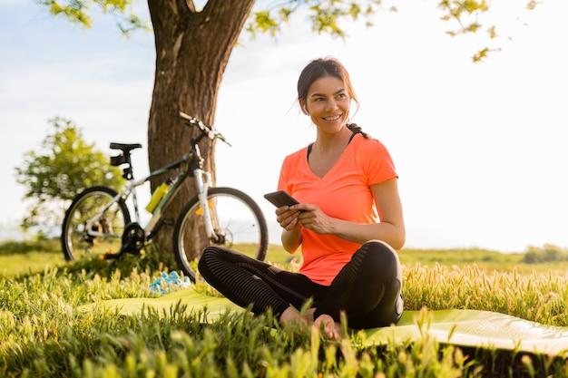 Hermosa mujer sonriente sosteniendo el teléfono haciendo deporte en la mañana en el parque