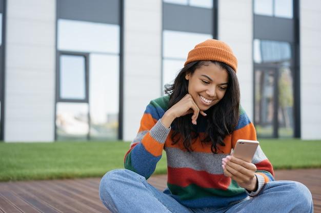 Hermosa mujer sonriente con teléfono móvil sentado en el parque