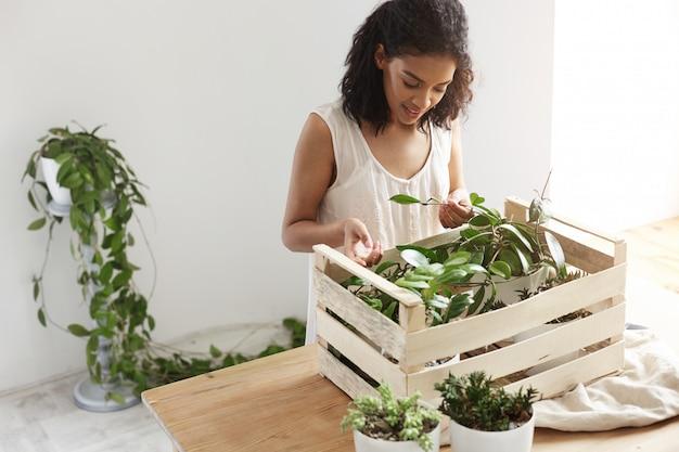 Hermosa mujer sonriente trabajando con plantas en caja en el lugar de trabajo pared blanca.