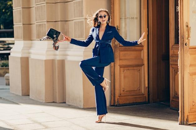 Hermosa mujer sonriente vestida con traje elegante y gafas de sol calle caminando sonriendo en tiempo soleado