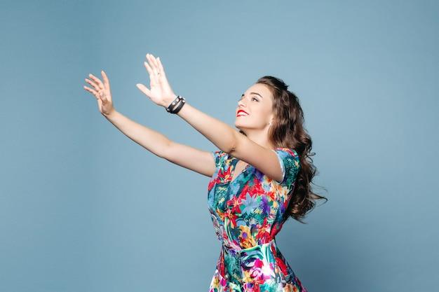 Hermosa mujer sonriente en vestido de flores tirando de su brazo hacia algo.