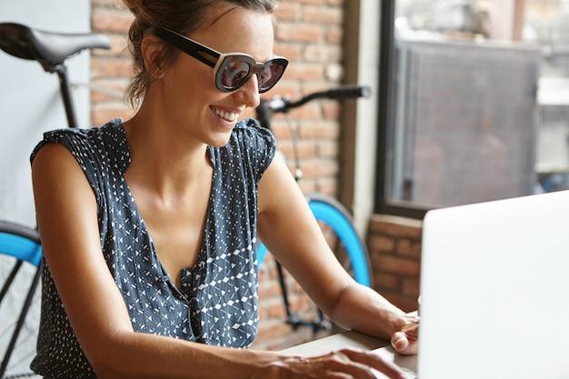 Hermosa mujer con una sonrisa feliz enviando mensajes a sus amigos en línea a través de las redes sociales, utilizando una conexión inalámbrica a internet