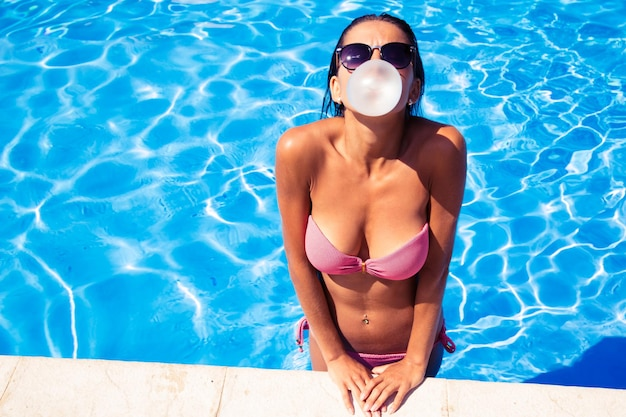 Hermosa mujer soplando burbujas con chicle en la piscina al aire libre