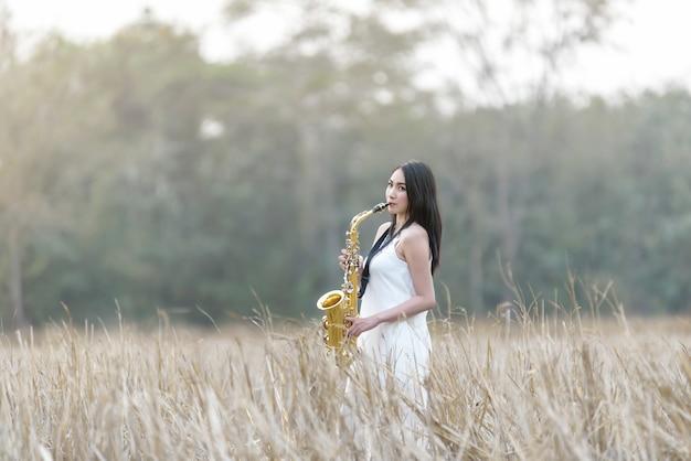 Hermosa mujer soplando saxofón en campo de hierba vintage
