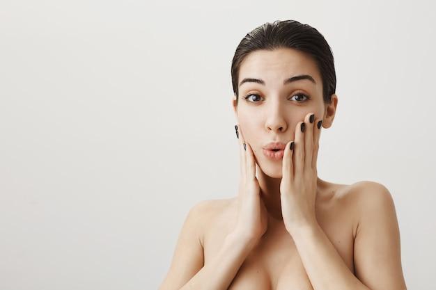 Hermosa mujer sorprendida de pie desnuda y reacciona a la sorpresa