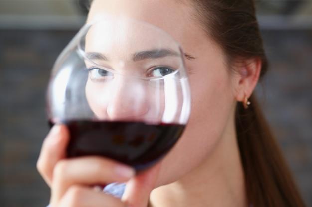 Hermosa mujer sostenga en brazos vaso de vino tinto