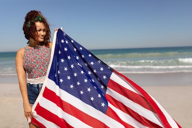 Hermosa mujer sosteniendo la bandera americana en la playa en el sunshifcane