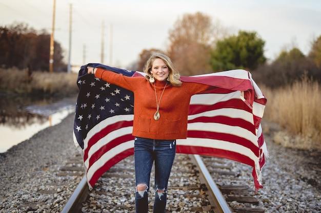 Hermosa mujer sosteniendo la bandera estadounidense mientras está de pie en el ferrocarril