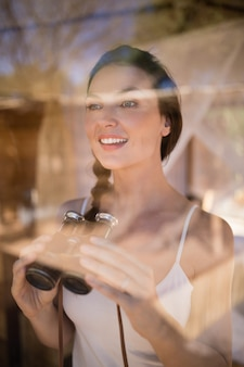 Hermosa mujer sosteniendo binoculares