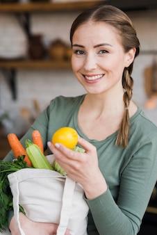 Hermosa mujer sosteniendo la bolsa con verduras orgánicas
