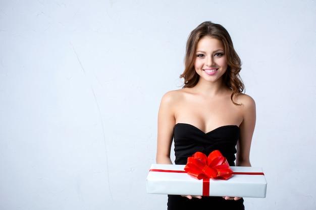 Hermosa mujer sosteniendo una caja de regalo blanca con cinta roja.