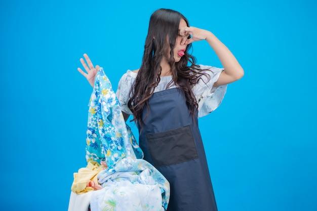 Hermosa mujer sosteniendo una canasta de ropa en azul