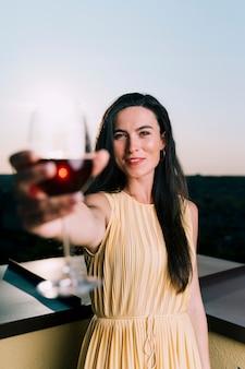 Hermosa mujer sosteniendo una copa de vino en primer plano borrosa