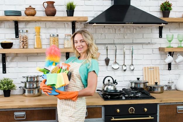 Hermosa mujer sosteniendo el cubo de herramientas y productos de limpieza en la cocina