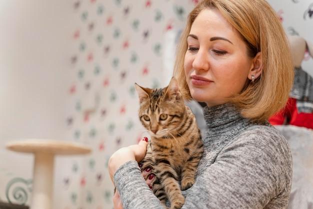 Hermosa mujer sosteniendo un gatito en la tienda de mascotas