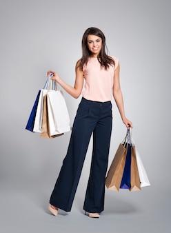 Hermosa mujer sosteniendo lleno de bolsas de la compra.