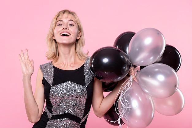 Hermosa mujer sosteniendo un montón de globos