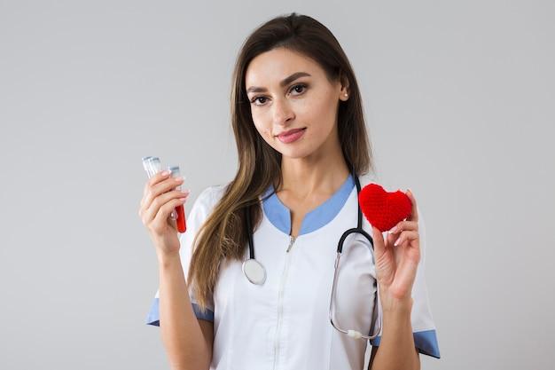 Hermosa mujer sosteniendo una muestra de sangre y corazón de felpa