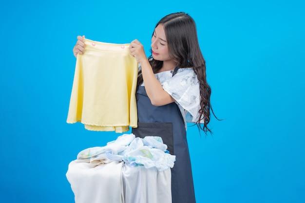 Una hermosa mujer sosteniendo un paño preparado para lavar en azul