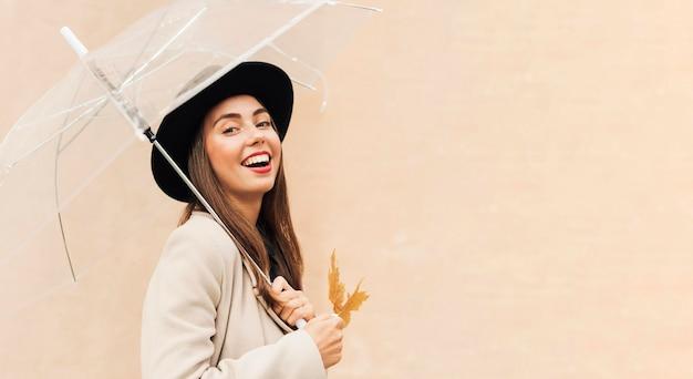 Hermosa mujer sosteniendo un paraguas con espacio de copia