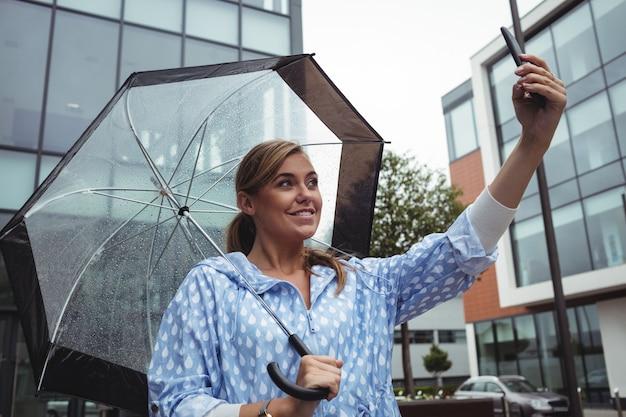 Hermosa mujer sosteniendo paraguas mientras toma selfie
