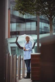 Hermosa mujer sosteniendo paraguas y de pie en la calle