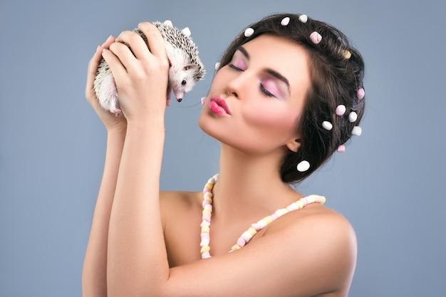 Hermosa mujer está sosteniendo un pequeño erizo lindo