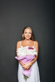 Hermosa mujer sosteniendo ramo de flores