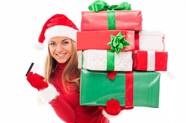Hermosa mujer sosteniendo regalos de navidad y tarjeta de crédito
