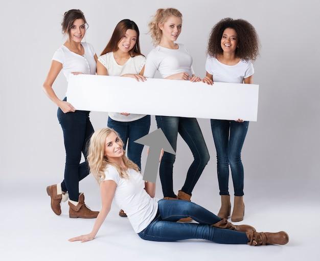 Hermosa mujer sosteniendo tablero blanco