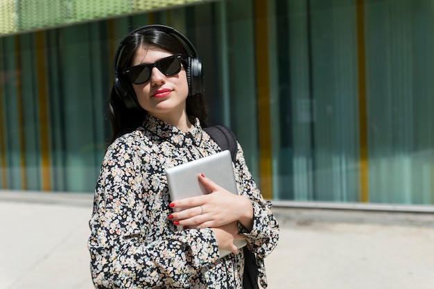 Hermosa mujer sosteniendo una tableta digital mientras está de pie en la calle