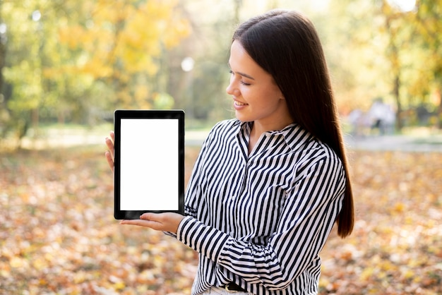 Hermosa mujer sosteniendo una tableta con maqueta