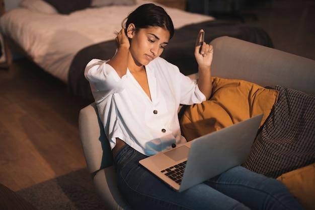 Hermosa mujer sosteniendo una tarjeta y trabajando en la computadora portátil