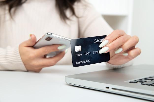 Hermosa mujer sosteniendo la tarjeta y usando el portátil para hacer compras en línea.