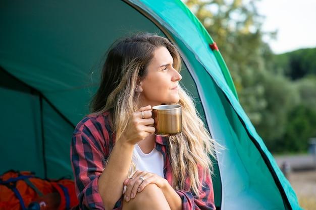 Hermosa mujer sosteniendo una taza de té, sentada en la tienda y mirando a otro lado. excursionista mujer caucásica relajarse en la naturaleza, disfrutar y acampar. turismo de mochilero, aventura y concepto de vacaciones de verano.