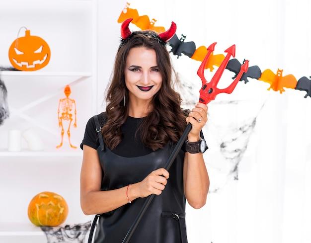 Hermosa mujer sosteniendo tridente de halloween