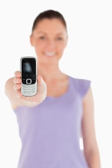 Hermosa mujer sosteniendo y mostrando su teléfono mientras está de pie