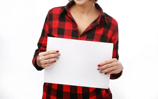 Hermosa mujer sostiene una tarjeta en blanco.