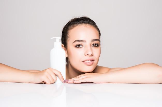Hermosa mujer spray facial en cosmetología de loción facial en pared blanca