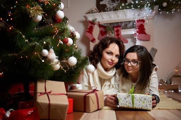 Hermosa mujer y su hija descansando bajo el tre de navidad