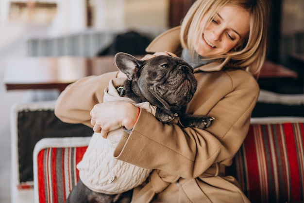 Hermosa mujer con su lindo bulldog francés en traje cálido