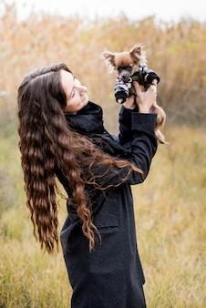 Hermosa mujer y su perro chihuahua en tela en el parque otoño