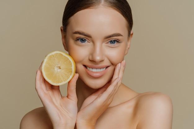 Hermosa mujer suave de pelo oscuro sonríe agradablemente posa con la mitad de limón para el cuidado de la piel y el cuerpo