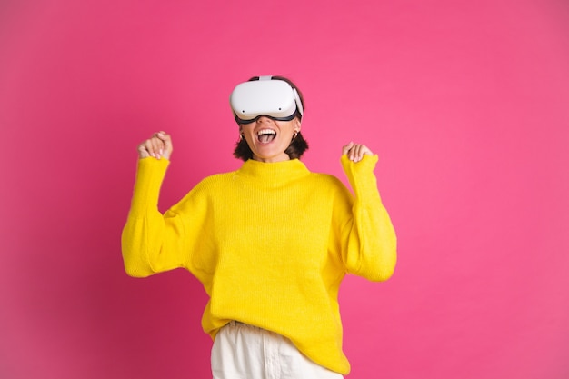Hermosa mujer en suéter amarillo brillante en rosa en gafas de realidad virtual feliz saltando apretando gesto de ganador de puño