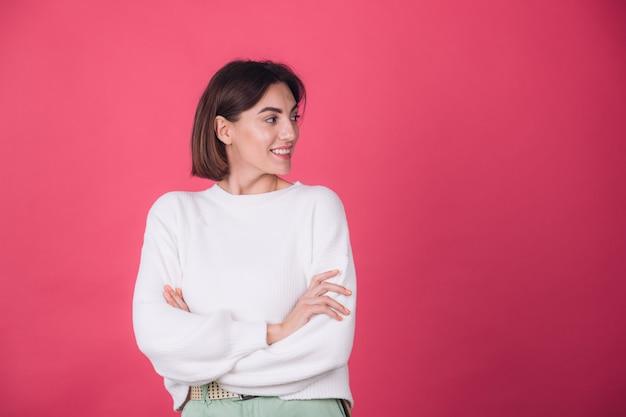 Hermosa mujer en suéter blanco casual en pared roja Foto gratis