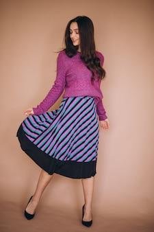 Hermosa mujer en un suéter morado y falda