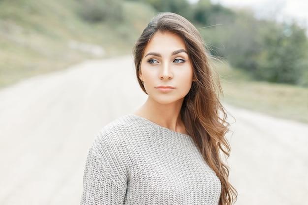 Hermosa mujer en suéter de punto vintage en la playa