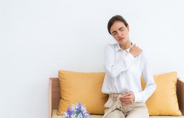 Hermosa mujer sufre dolor en el hombro mientras está sentado en el sofá en la sala de estar