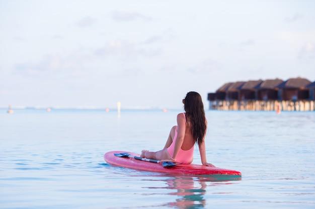 Hermosa mujer surfista surfeando en mar turquesa